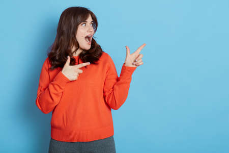 Excited dark haired female wearing casual attire pointing aside with both hands, looking away with widely opened mouth, dark haired female showing direction, isolated over blue background.