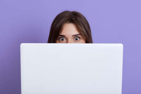 Scared dark haired female hiding behind laptop and looking at camera with eyes full of fear, being afraids of something, wants somebody do not see her, isolated over lilac background. Stockfoto
