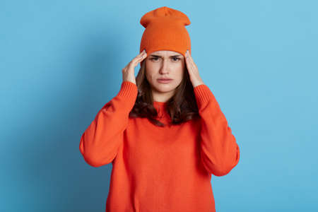 Woman suffering from headache, touching temples with both hands, has migraine, wearing casual orange jumper and hat, needs treatment, health care, posing isolated over blue background.