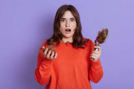 Beautiful woman with shocked facial expression, being upset of hair loss, needs treatment, holding comb with lots hair on it, wearing sweater, stands with opened mouth isolated over lilac background. Stockfoto