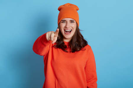 Happy positive laughing female wearing jumper and hat pointing finger to camera and makes fun of somebody, being in good mood, ridiculing and satirizing, isolated over blue background. Stockfoto