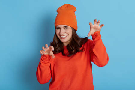 Happy positive European female wearing casual orange jumper and hat showing claws gesture and looking directly at camera with smile, posing isolated over blue background.