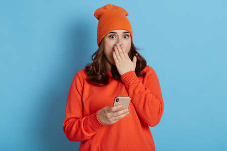 Shocked female with phone in hands hearing astonishing news, has scared expression, covering mouth with palm, looks at camera with big eyes, isolated over blue background.