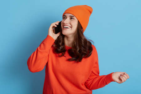 Happy dark haired woman in orange sweater and hat has pleasant conversation via smart phone, looking away with positive expression, holding cell phone isolated over blue background.