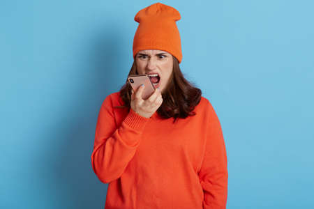 Angry aggressive dark haired female screaming while talking phone, expressing negative emotions, wearing casual hat and jumper, posing isolated over blue background. Stockfoto