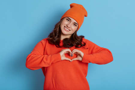 Young Caucasian female wearing orange sweater and hat making heart gesture with hands and looking directly at camera with happy expression, isolated over blue background.