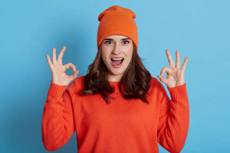 Young European excited female wearing orange sweater and cap looking at camera with opened mouth and showing ok signs with both hands, dark haired girl isolated over blue background.