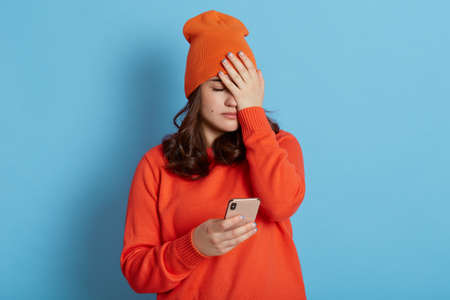 Frustrated female wearing casual clothing, covering face with palm, holding phone in hands, forget something important, making gross mistake, being sad, isolated over blue background.