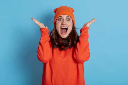 Woman expressing pleasant surprise, raises hands and looking at camera with positive shocked look, keeps mouth opened, wearing orange hat and jumper, isolated over blue background. Stockfoto