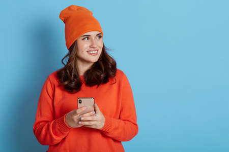 Caucasian female wearing casual clothing posing with smart phone in hands and looking away with pleasant smile and dreamy facial expression, isolated over blue background. Copy space.