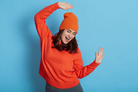 Young Caucasian female dresses jumper and hat dancing happily, celebrating her success, has great news, raising arms and keeps mouth open, isolated over blue background.
