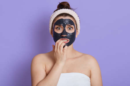 Scared woman being wrapped in white towel biting fingers nails while looking directly at camera, doing cosmetic procedures, stands with black mask on face, isolated over lilac background.