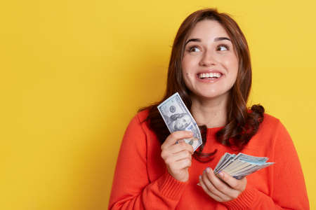 Happy dark haired girl wearing orange sweater holding money in hands, looking away with dreamy look, thinks how to spend big sum, posing isolated over yellow background.