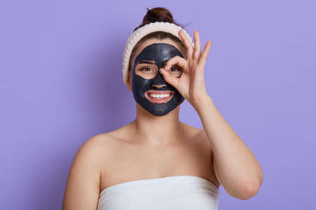 Happy female wrapped in towel and wears hair band making cosmetology procedures, stands with black mask on face, cover eye with ok sign like binoculars, isolated over lilac background. Stockfoto