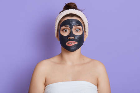 Surprised female applying black face mask looking directly at camera with big eyes, biting lips, doing cleansing procedures for face, skin care, isolated over lilac background.