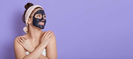 Smiling young adult woman in hair band with black facial mask doing cosmetology procedures, looking aside, crosses hands on shoulders, copy space, isolated over lilac background. Stockfoto