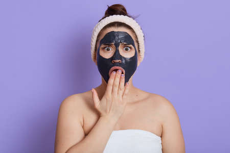 Shocked female with black moisturizing mask on face covering open mouth with palm, being unpleasant surprised, wearing hair band, wrapped in towel, isolated over lilac background. Stockfoto