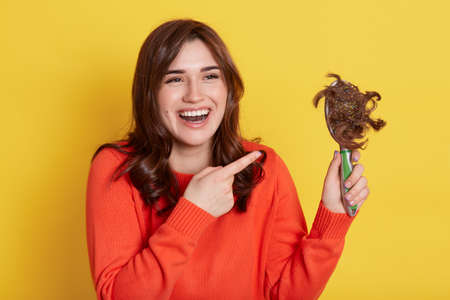 Dark haired girl in orange sweater holding comb with lost hair and pointing with index finger at it, laughing happily, having fun, isolated over yellow background. Stockfoto