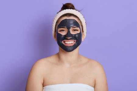 Satisfied woman with black cleansing facial mask looking at camera with happy smile, relaxing while making skin care procedures, posing with bare shoulders, isolated over lilac background.