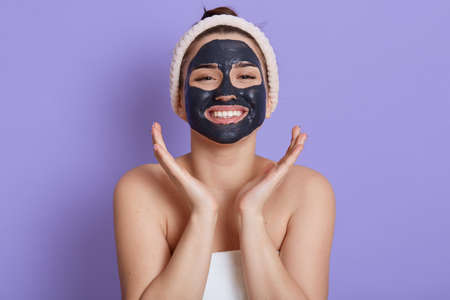 Happy female doing moisturizing procedures for skin of face, looks at camera with smile, keeping palms near cheeks, expressing joy, cosmetology manipulation, isolated over lilac background.