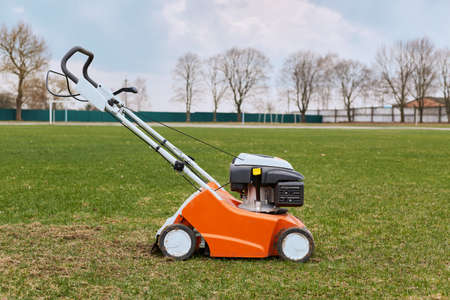 Mowing or cutting long grass with lawn mower. Gardening, taking care of sward. Side view of special equipment in field on background of grass, trees and sky,