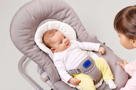 Pretty newborn child in bouncer rocking chair looking with curious expression at her sister, exploring world around, posing isolated over white background, children playing together.