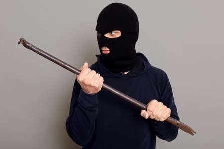 Man thief with handy crowbar looks away, wants to break open door or lock, dresses in balaclava and turtleneck, dangerous bandit commits a crime, posing isolated over gray background. 版權商用圖片
