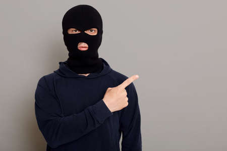 Male thief dressed in black turtleneck and robbery mask points his index finger to side, copy space for promotional text or advertisement, posing isolated over gray background. 版權商用圖片