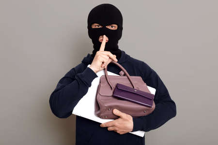 Man burglar holds laptop, wallet and woman's purse in his hands, holds finger to his mouth, shows gesture quietly, the robber wearing mask and black turtleneck, isolated over gray background.