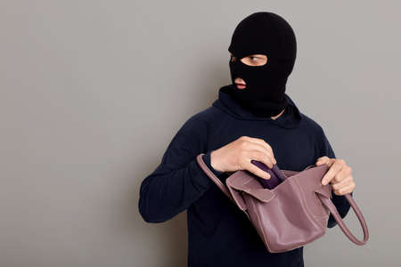 Insidious male villain in balaclava stands with stolen women's bag and wallet, afraid that he will be caught, turns around and looks carefully back, isolated over gray background.
