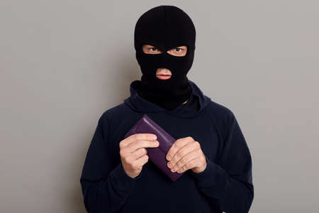 Serious young man burglar in robbery mask and black sweater holds tightly wallet that he just stole, hoping for huge amount of money, standing isolated over gray background.