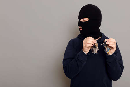 Surprised criminal thief looks to side and with contented expression on his face, holds in both hands bundle of keys, copy space for advertisement, posing isolated over gray background. Standard-Bild