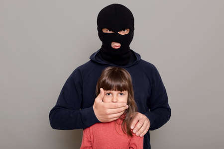 Man burglar in balaclava kidnapped little preschooler girl, holds her hostage, covers her mouth with his hands, asks for ransom for kidnapped child, posing isolated over gray background.