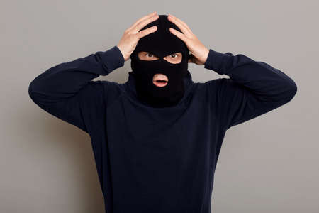 Shocked and frightened criminal, thief catching on place of committing crime, looking at camera with frightened eyes, holding his head, does not understand what to do, isolated over gray background.