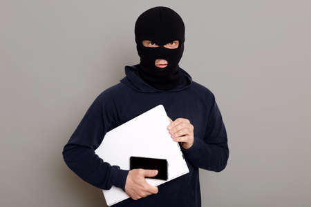 Satisfied man robber steals laptop beech and phone, being dressed in robber mask and black turtleneck, looks at camera firmly holds stolen things, posing isolated over gray background.