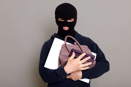 Serious male thief holding bunch of stolen things, laptop, wallet and woman's handbag, robber wearing mask and black turtleneck, burglar isolated over gray background.