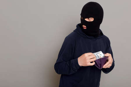 Man steals wallet with money, runs away, turns back, being afraid of persecution, wearing robbery mask and black turtleneck, advertising space, posing isolated over gray background. 版權商用圖片
