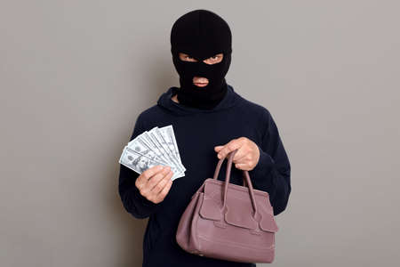 Angry serious thief dressed in balaclava and black turtleneck looks at camera and holds money and stolen women's handbag, robbery, posing isolated over gray background. 版權商用圖片