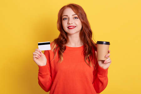 Caucasian smiling female with pleasant appearance looking at camera smiling, showing plastic bank card and take away coffee, buying online, isolated over yellow background.