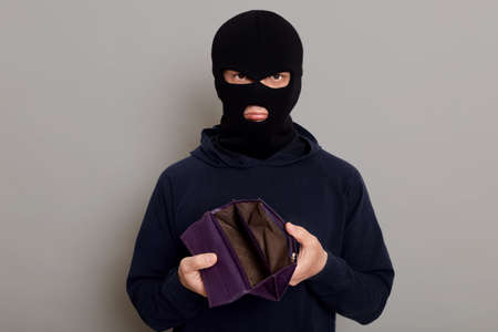 Upset burglar dressed in black turtleneck and balaclava holding empty wallet, feeling frustrated, looking at camera with pouting lips, being unhappy with theft, isolated over gray background. 版權商用圖片