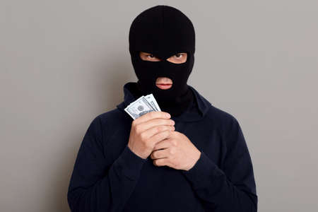 Angry burglar guy looks at the camera with a forged expression and holds the stolen money in his hands, happy with the work done, isolated on gray background.