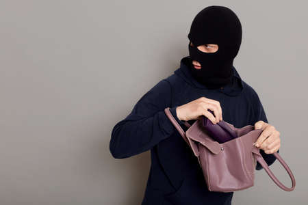 Profile of a thief guy with a masked face, a burglar stole a purse and a woman's handbag looking back, afraid to be caught, copy space, isolated on gray background.