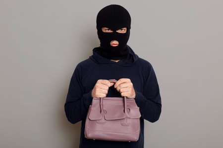 A young guy thief is dressed in a black hoodie and robbery mask, holds a woman's bag with both hands, stole other people's things, looks at the camera, isolated on gray background.