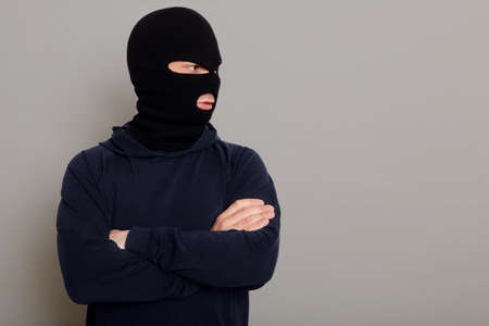 A criminal man in bandit mask and a black hoodie stands with folded hands on his chest, looking to the side, copy space for advertising text, isolated on gray background.