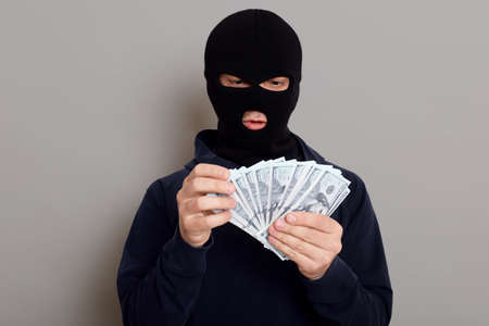 Robber man dressed in black hoodie stands with disguised face and holds a lot of money in his hands, stole a large amount, counts bills, isolated over gray background. 版權商用圖片