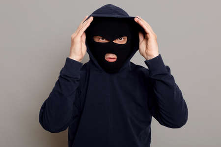 Concentrated young criminal man in a bandit mask dressing a hood, going to rob someone, trying to disguise himself more, looking directly at camera, isolated on gray background.