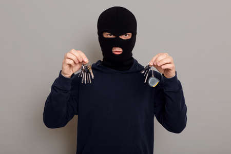 A criminal man in a black hoodie and a mask holds a bunch of keys in both hands, is about to open someone else's apartment with the keys stolen, looks at camera, isolated on gray background.