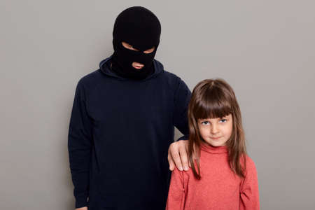 Terrible criminal man wearing black hoodie and robber mask holds a little preschool girl hostage, stands and holds child by the shoulder, kidnapping, isolated on gray background. 版權商用圖片