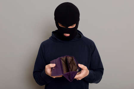 Frustrated guy thief dressed in a black hoodie and a robbery mask, holding a stolen open empty wallet in his hands, looks upset, isolated on gray background. 版權商用圖片