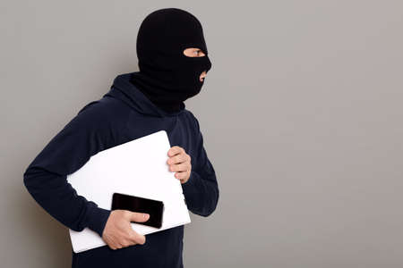 Side view of a criminal guy escaping with a stolen laptop, a woman's bag and a wallet, the robber is wearing a black hoodie, his face is disguised, copy space, isolated on gray background